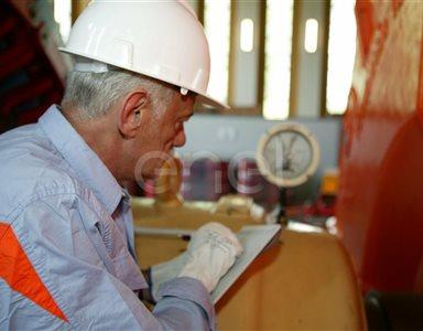 Operaio all'interno della sala macchine: lettura dati da un manometro del gruppo turboalternatore