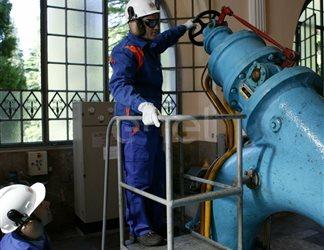 Operai, con casco, occhiali protettivi e cuffie antirumore, in sala macchine controllano il gruppo turboalternatore