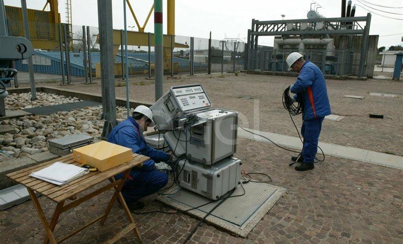 Operai eseguono test di controllo su un trasformatore trifase all'interno della stazione elettrica di trasformazione della centrale di Presenzano