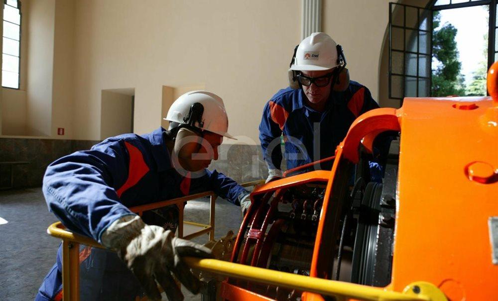 Due Operai, con casco, occhiali protettivi e cuffie antirumore, in sala macchine controllano il funzionamento dell'eccitatrice di una turbina