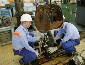 Operai agganciano una ruota dentata al carro ponte all'interno dell'officina della centrale di Sulcis