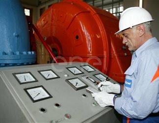 Operaio all'interno della sala macchine: operazioni di controllo su un gruppo turboalternatore