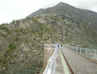 Coronamento della diga di Alpe Gera con operaio e turisti