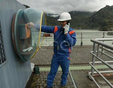 Operaio al telefono sul coronamento della diga di Alpe Gera